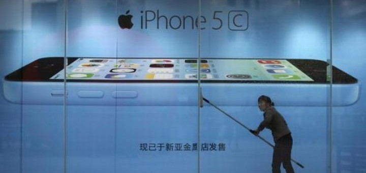 a worker cleaning in front of an iPhone 5C advertisement at an apple store in Kunming