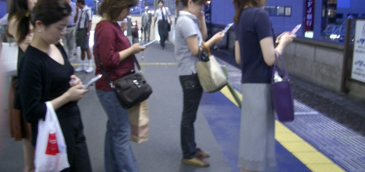 people using smartphones in public